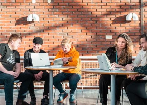 Bilde av fem studenter og en lærer som studerer sammen og arbeider med gruppearbeid med bøker og PC.